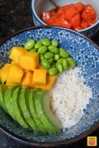 Sliced avocado, diced mango, and edamame over rice in a white and blue bowl