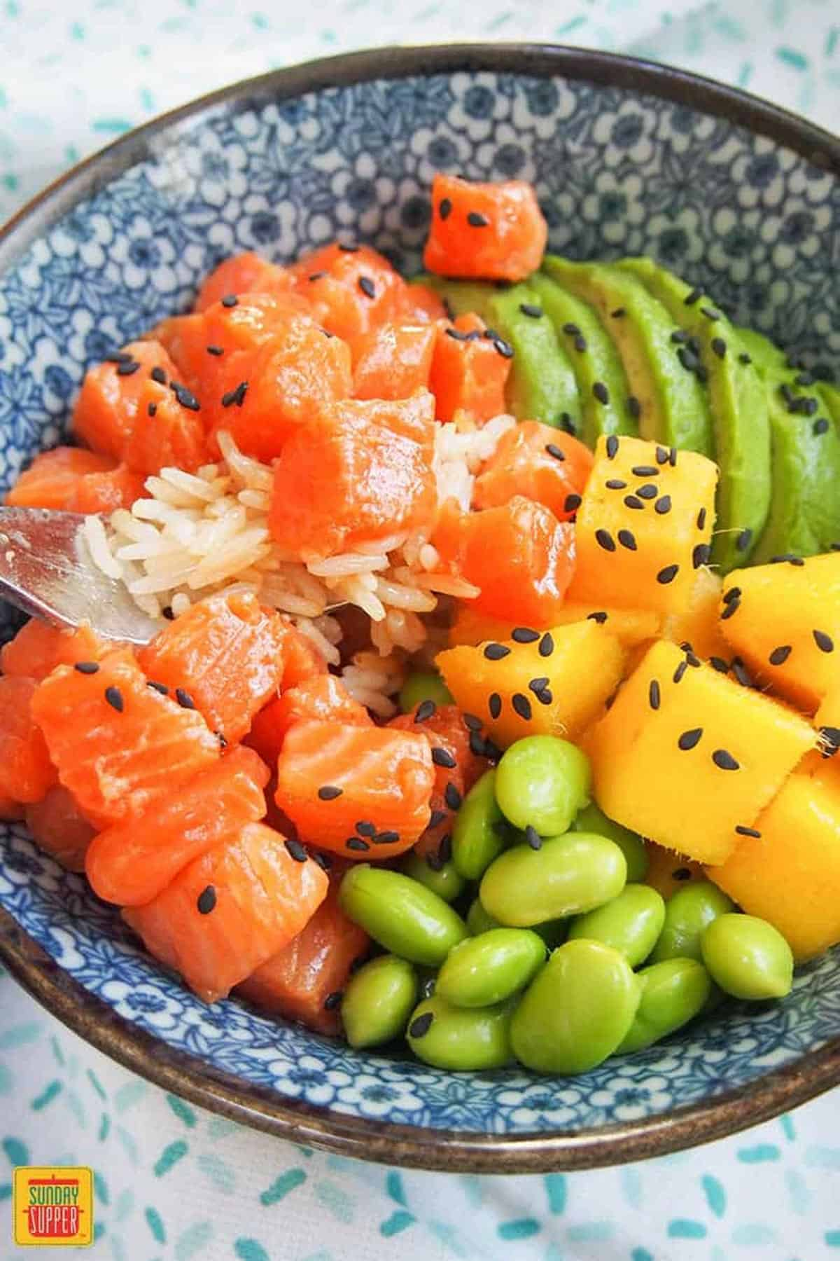 A forkful of diced salmon in a salmon poke bowl next to mango, edamame, and sliced avocado