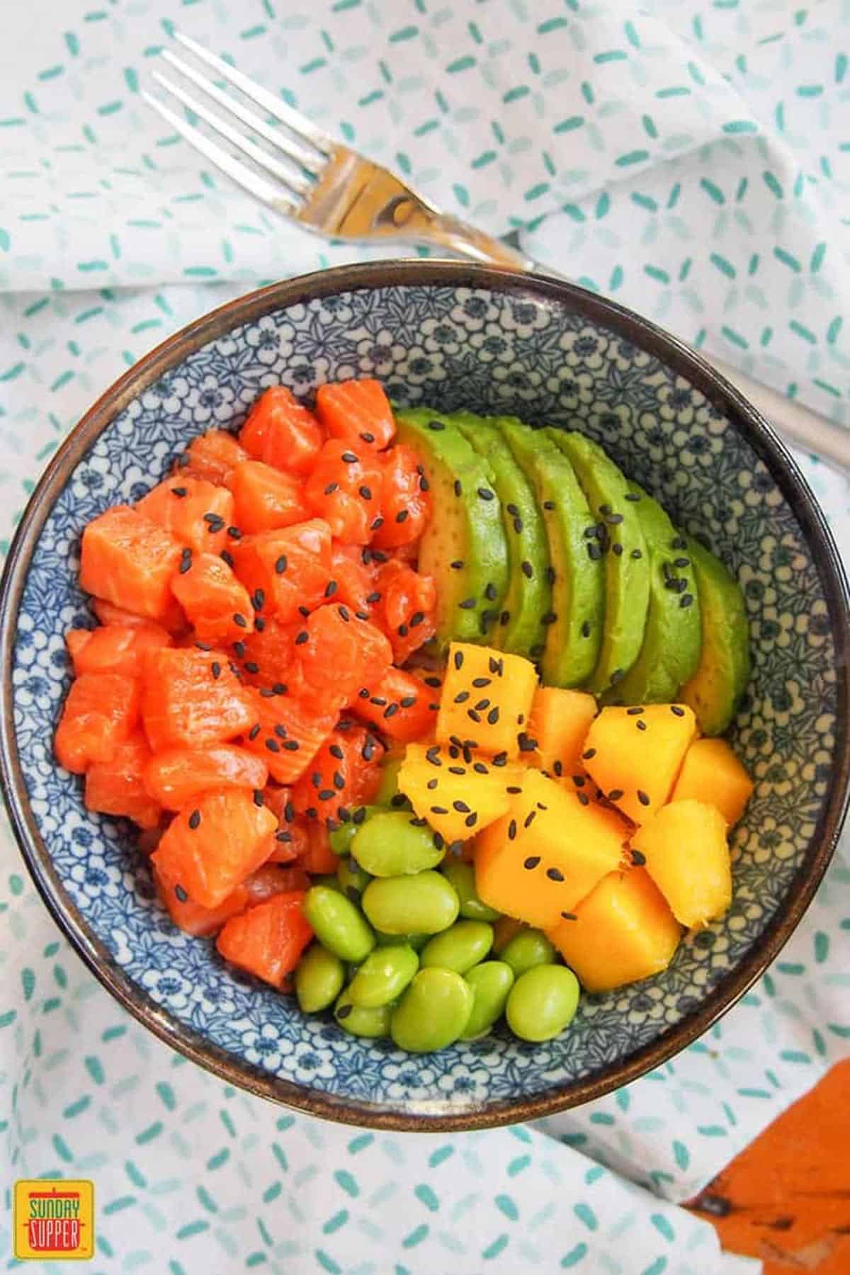 Top-down view of salmon poke bowl with avocado slices, diced mango, and edamame, topped with sesame seeds