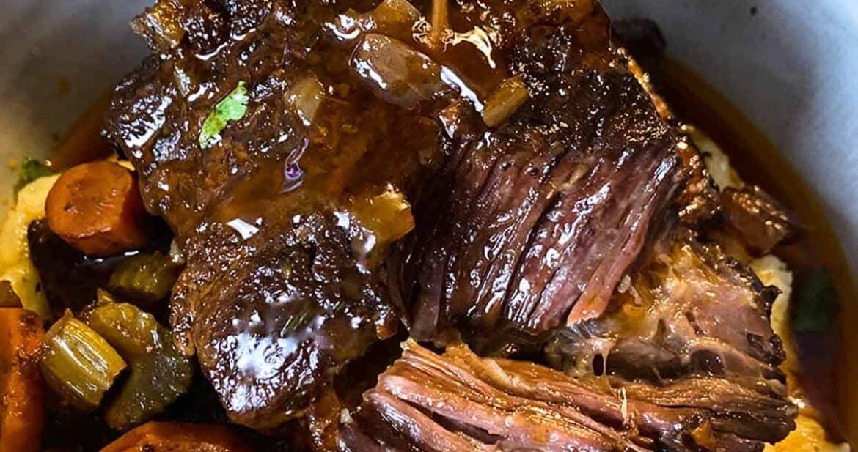 Slow cooker short ribs served over vegetables