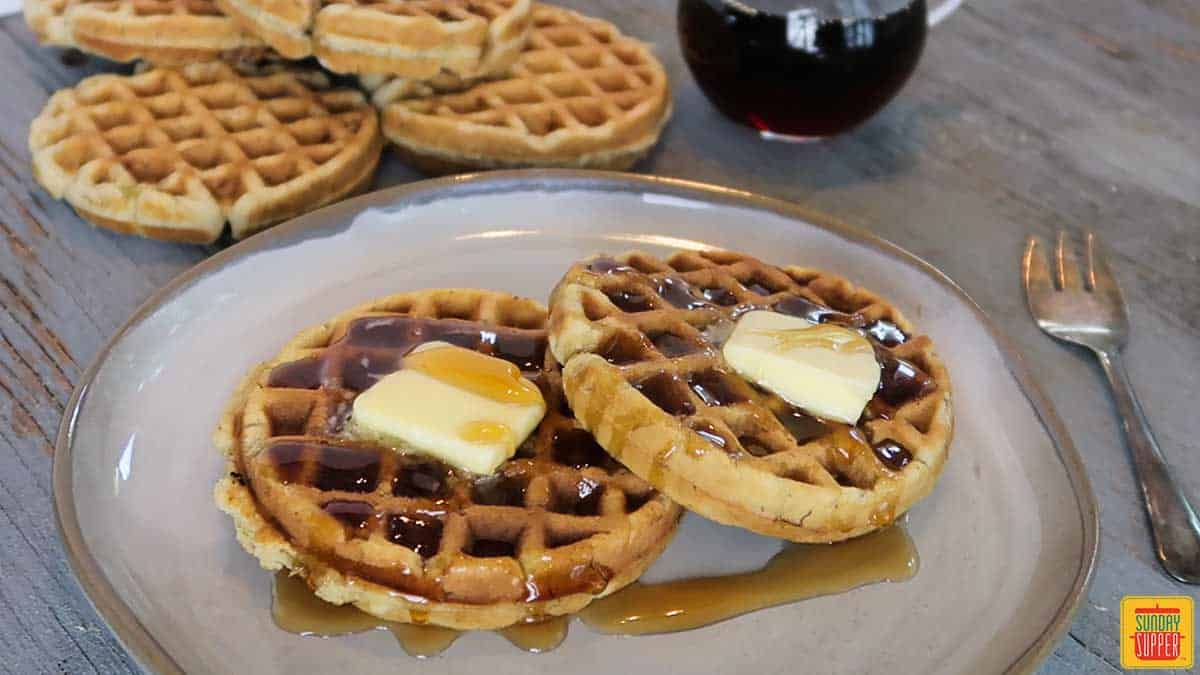 Two banana bread waffles on a plate with butter on top