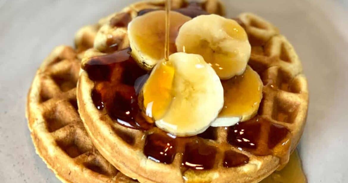 Pouring syrup onto two banana bread waffles topped with banana slices
