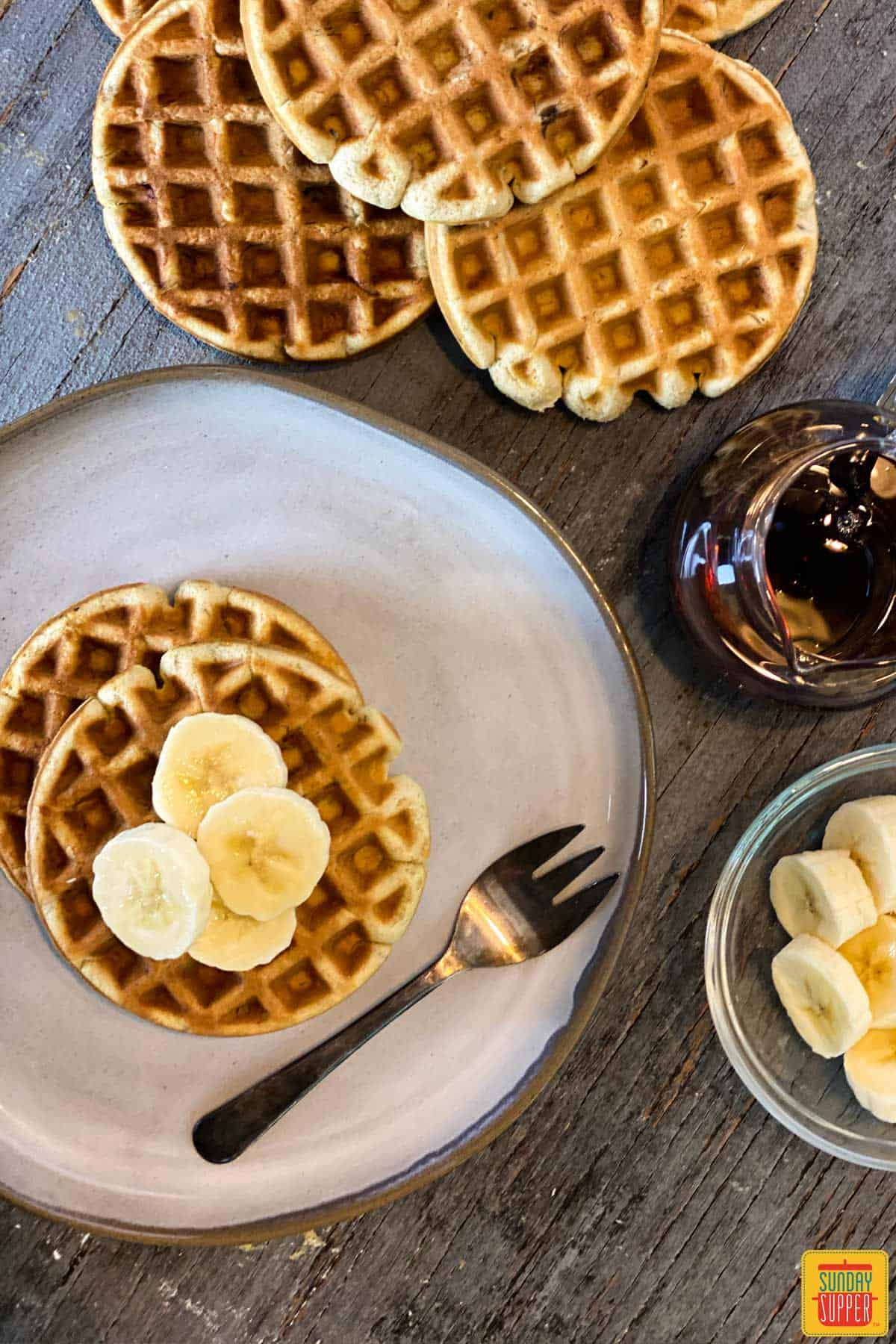 A plate of two banana waffles with a fork to the side