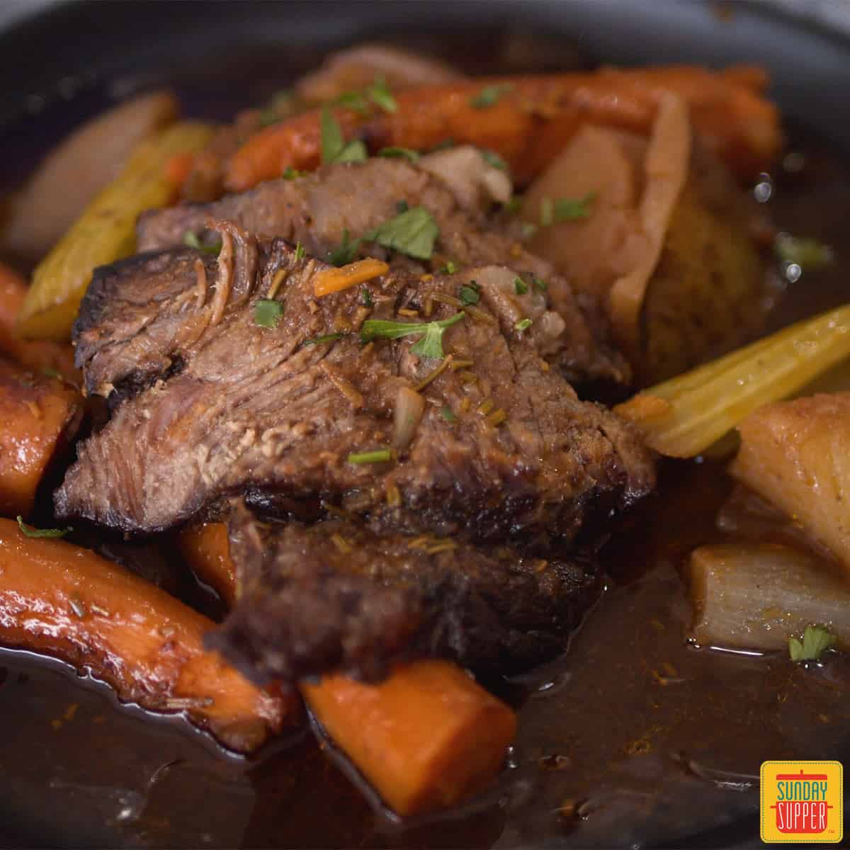 Chuck roast up close with vegetables and gravy