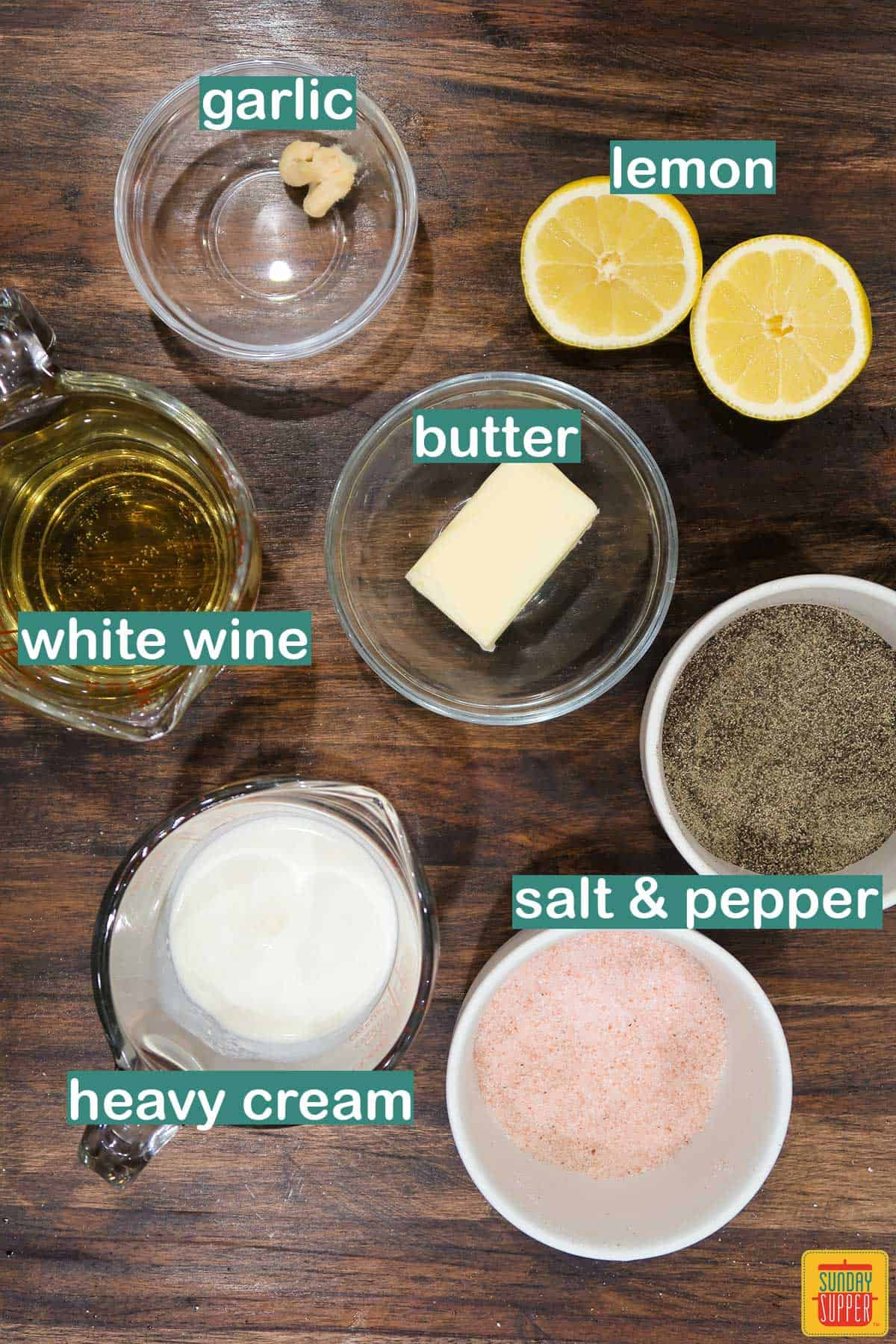 Ingredients to make lemon butter sauce labeled on a brown wood surface