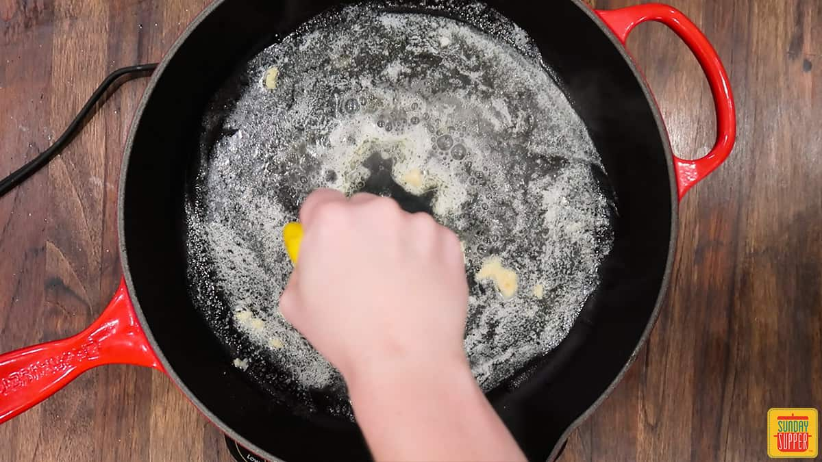 Squeezing lemon into a skillet with garlic and butter
