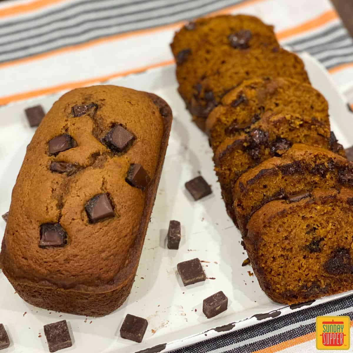A loaf of Instant Pot Pumpkin Chocolate Chip Bread with another loaf sliced next to it