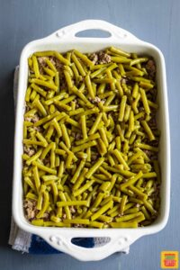 Casserole dish filled with ground beef topped with green beans