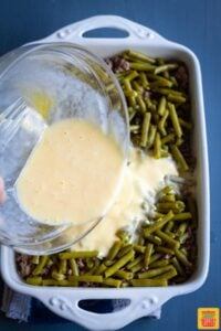 Pouring egg mixture over green beans and ground beef in casserole dish