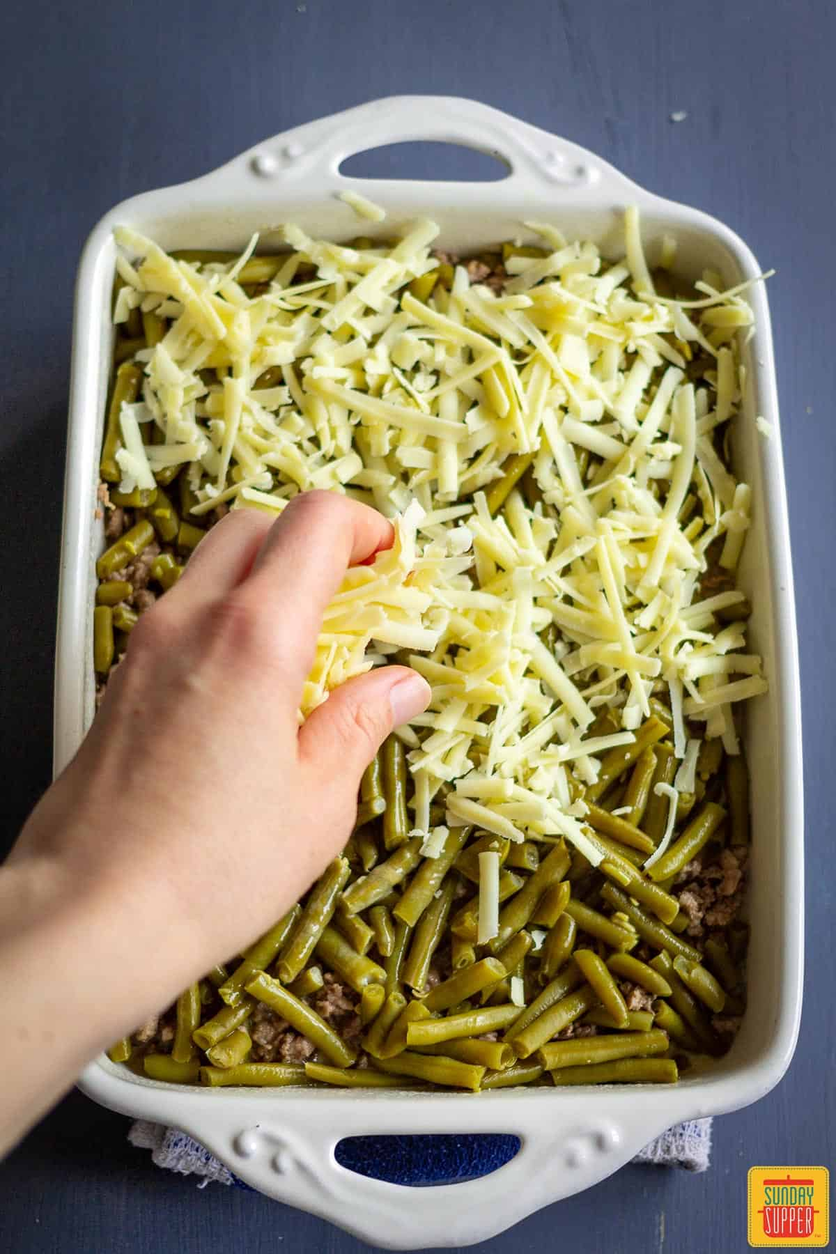 Adding grated white cheddar to casserole dish of green beans and ground beef