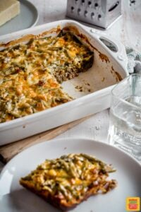 Easy cheeseburger casserole in a white casserole dish next to a plate with a single serving