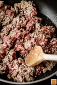 Cooking ground beef in a skillet with a wooden spoon