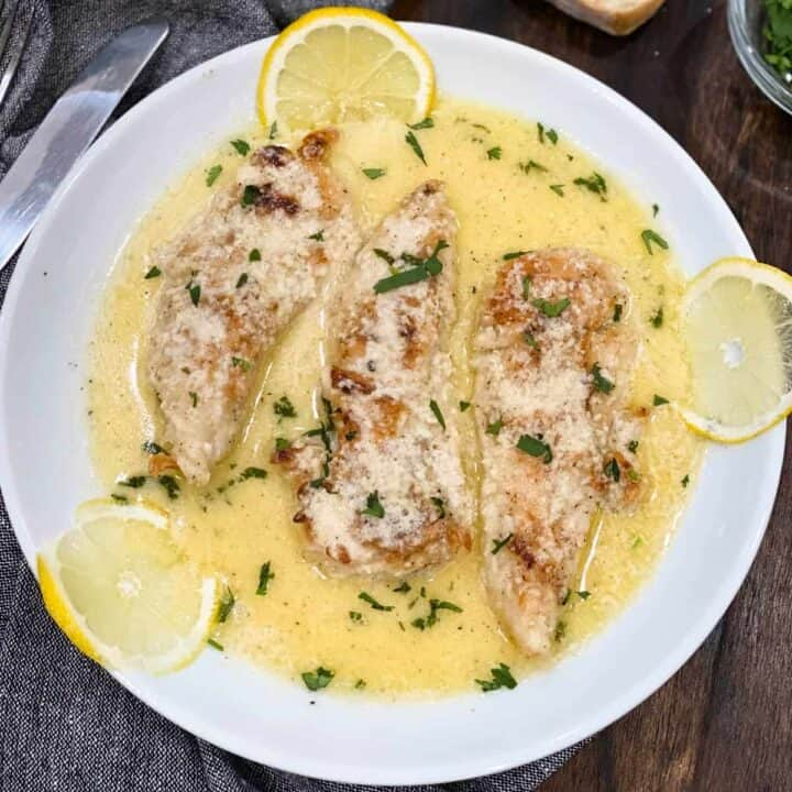 lemon butter chicken on a white plate with three lemon slices and parsley on top