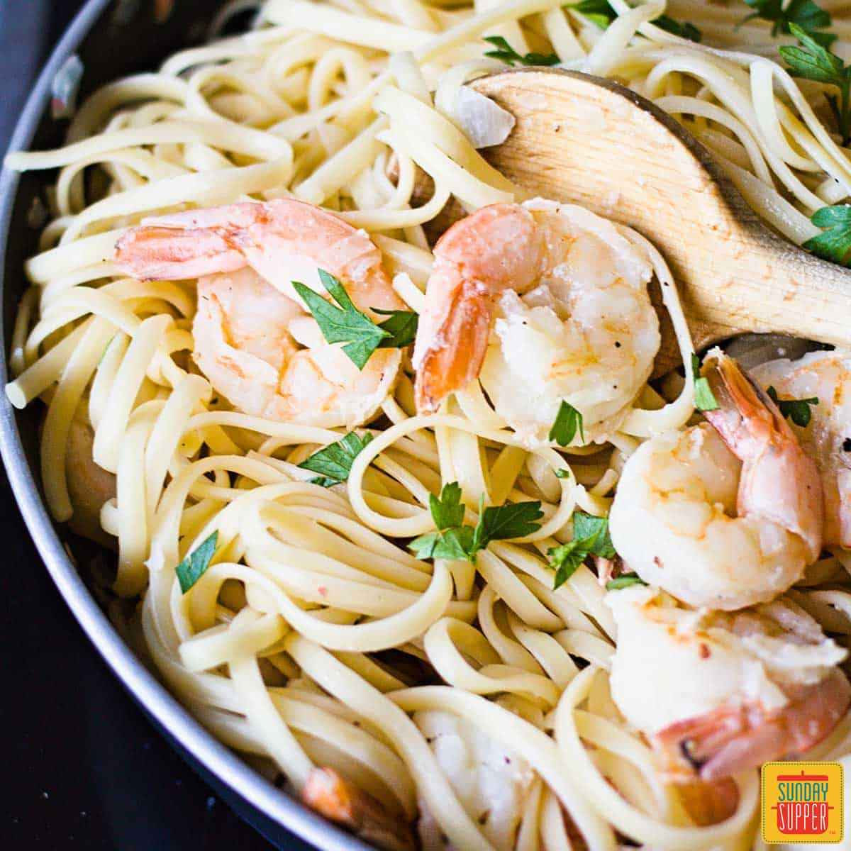 Shrimp scampi linguine in a skillet with a wooden spoon