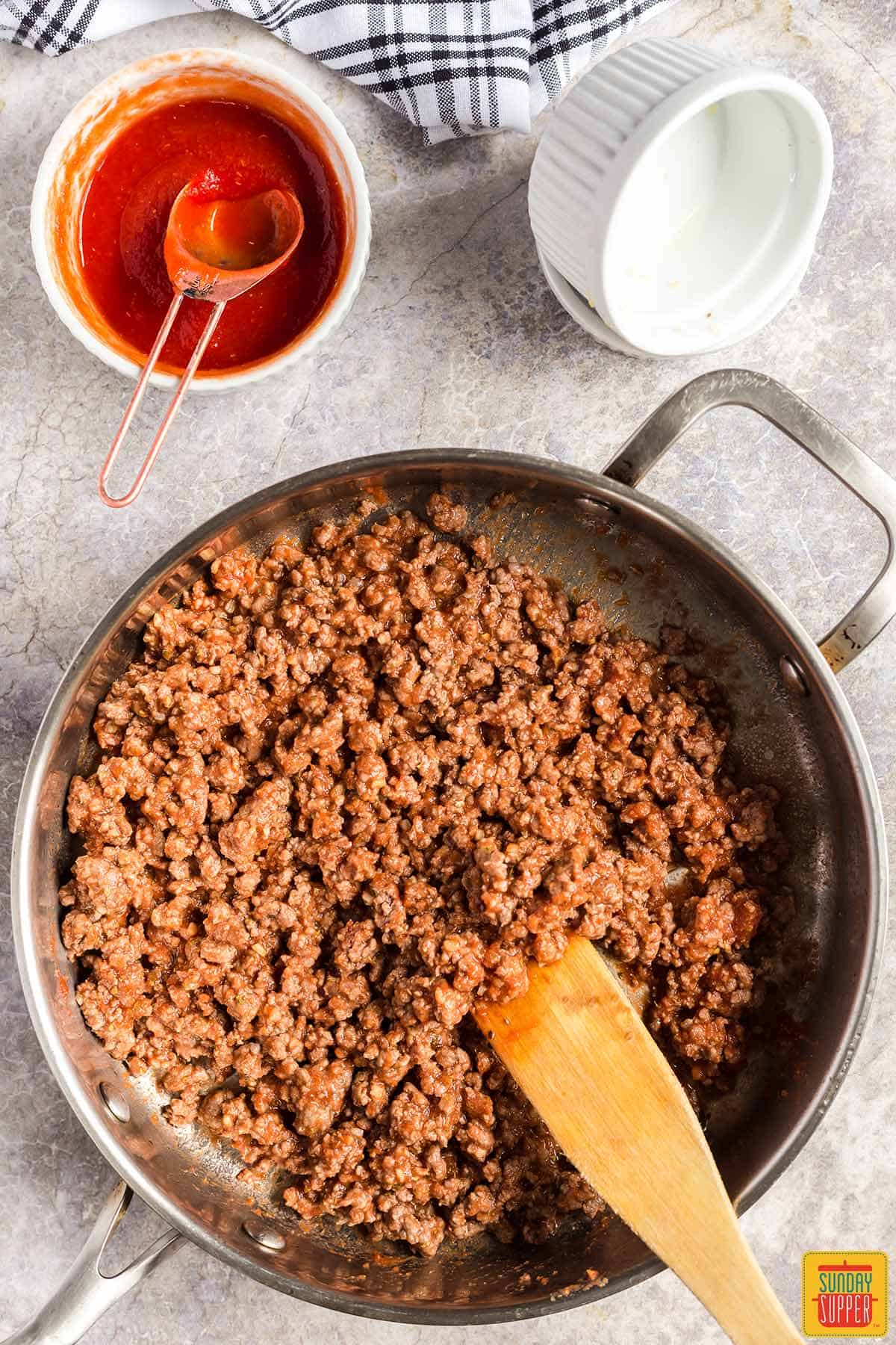 Ground beef mixed with tomato sauce and seasoning in a skillet
