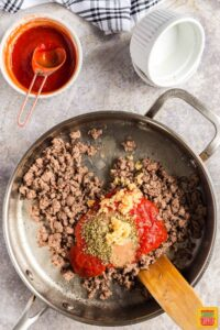 Adding tomato sauce and seasoning to ground beef in a skillet