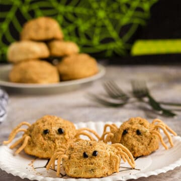 Three potato spiders on a paper plate with more potato balls on a plate in the background