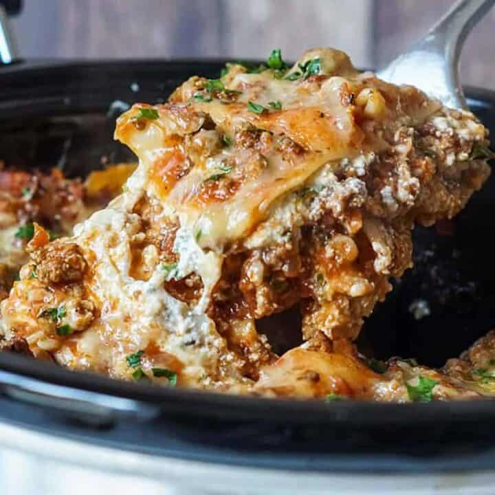 Lifting slow cooker lasagna out of the crockpot with a serving spoon