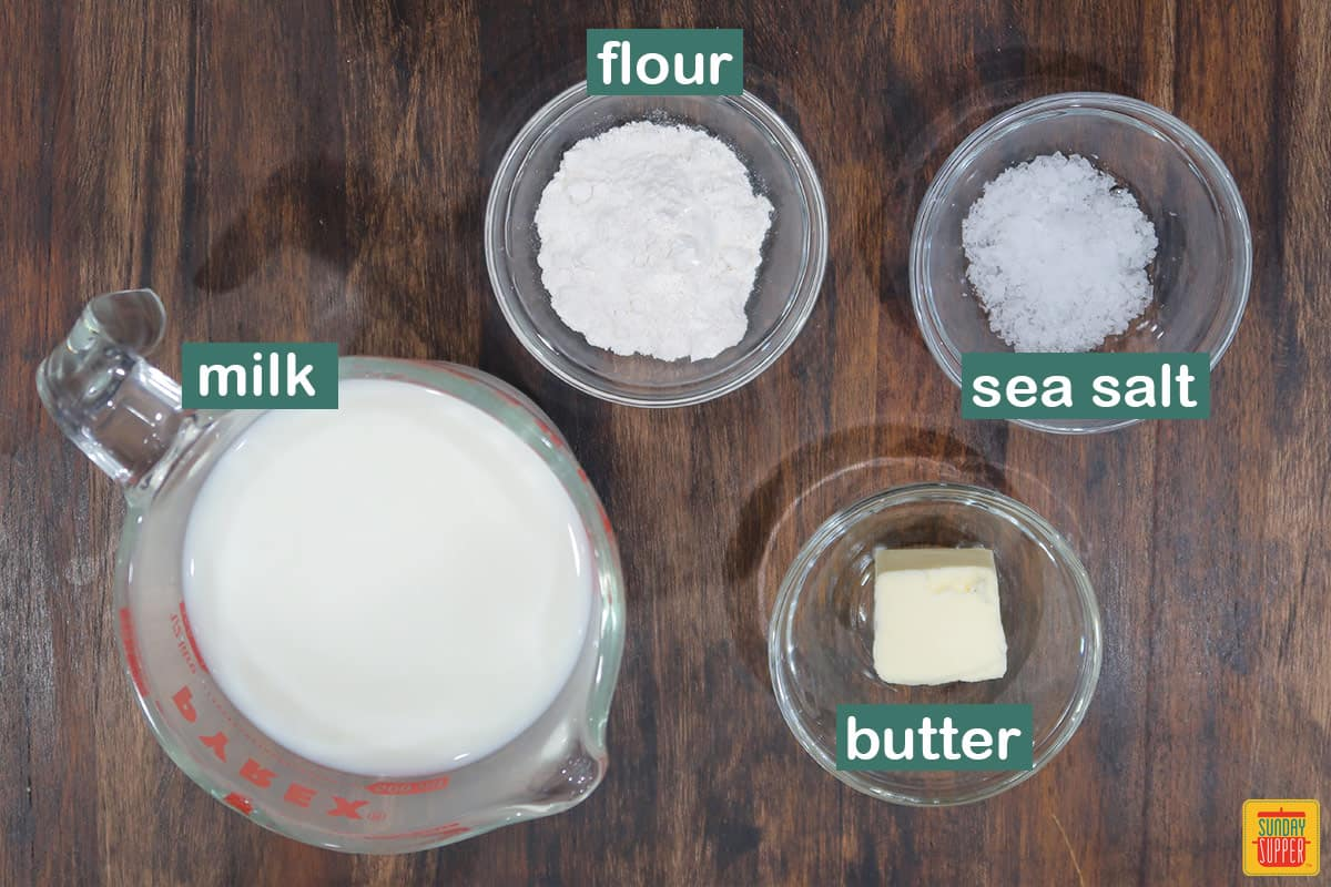 bechamel sauce ingredients labeled on a wooden surface