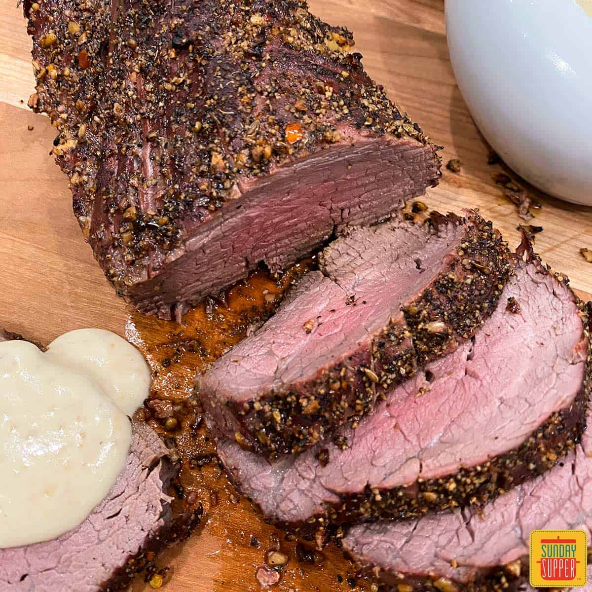 Grilled beef tenderloin cut into slices on a cutting board