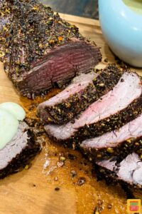 Sliced beef tenderloin on a cutting board