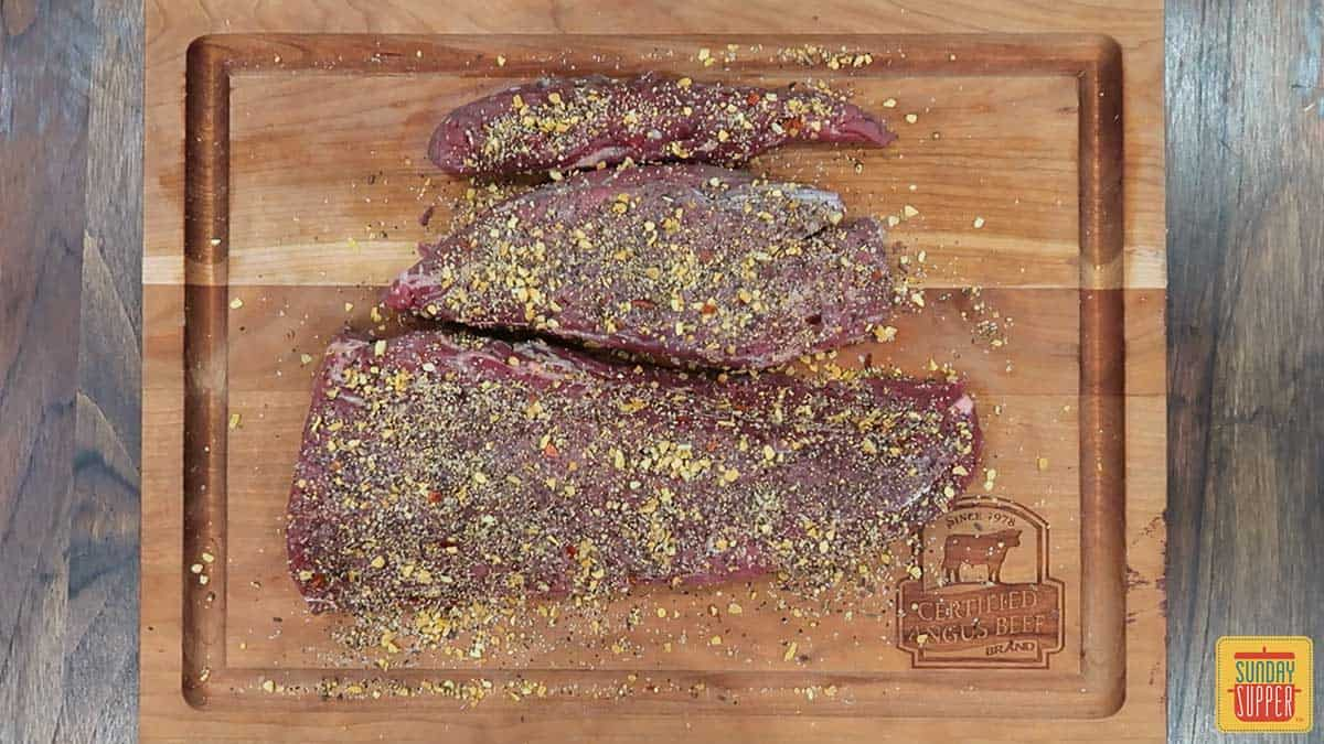 Raw beef tenderloin coated with rosemary sea salt mixture on a cutting board