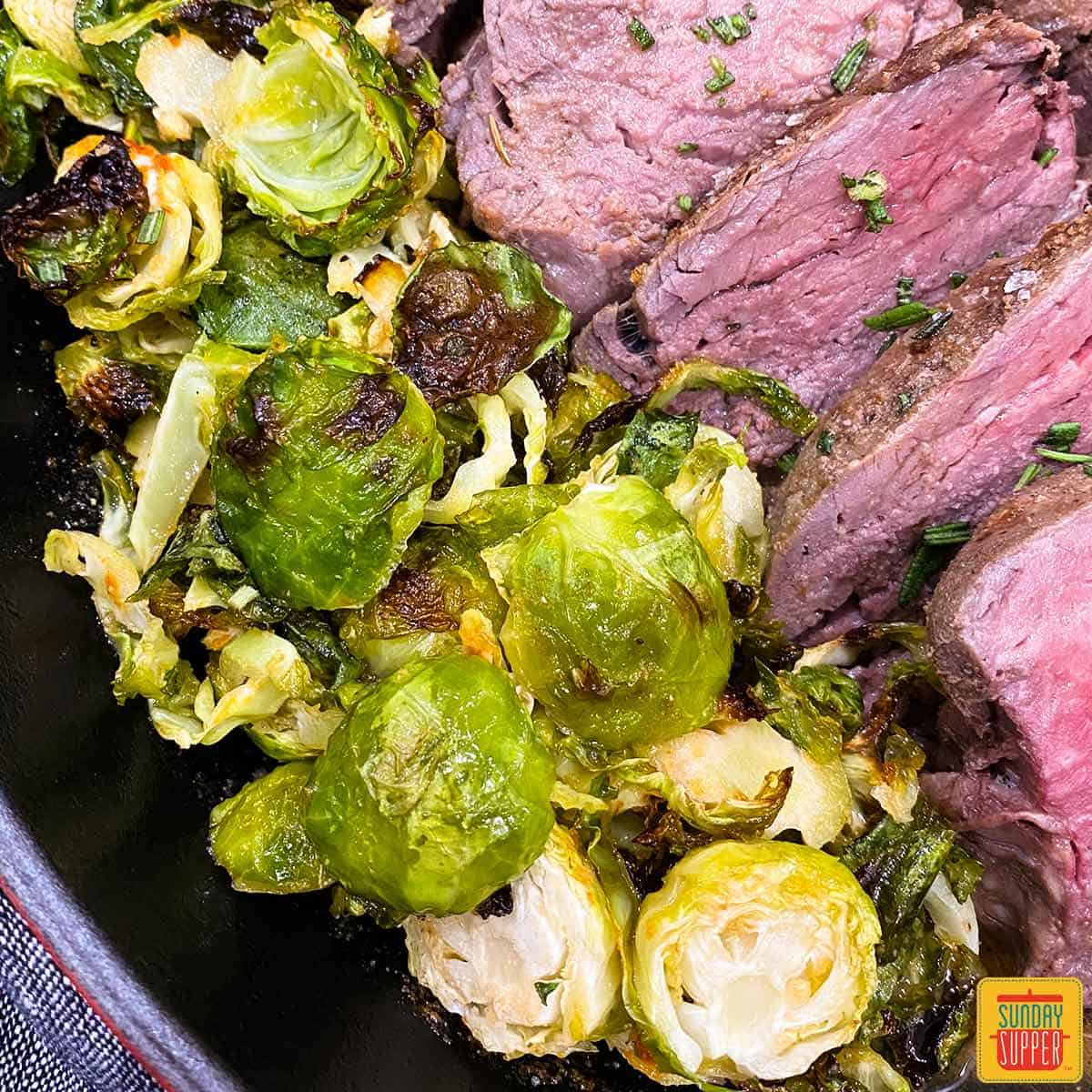 Close up of roasted brussels sprouts next to sous vide tenderloin in a skillet