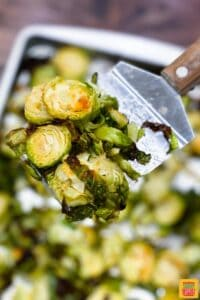 A metal spatula with roasted brussels sprouts over a baking sheet of sprouts