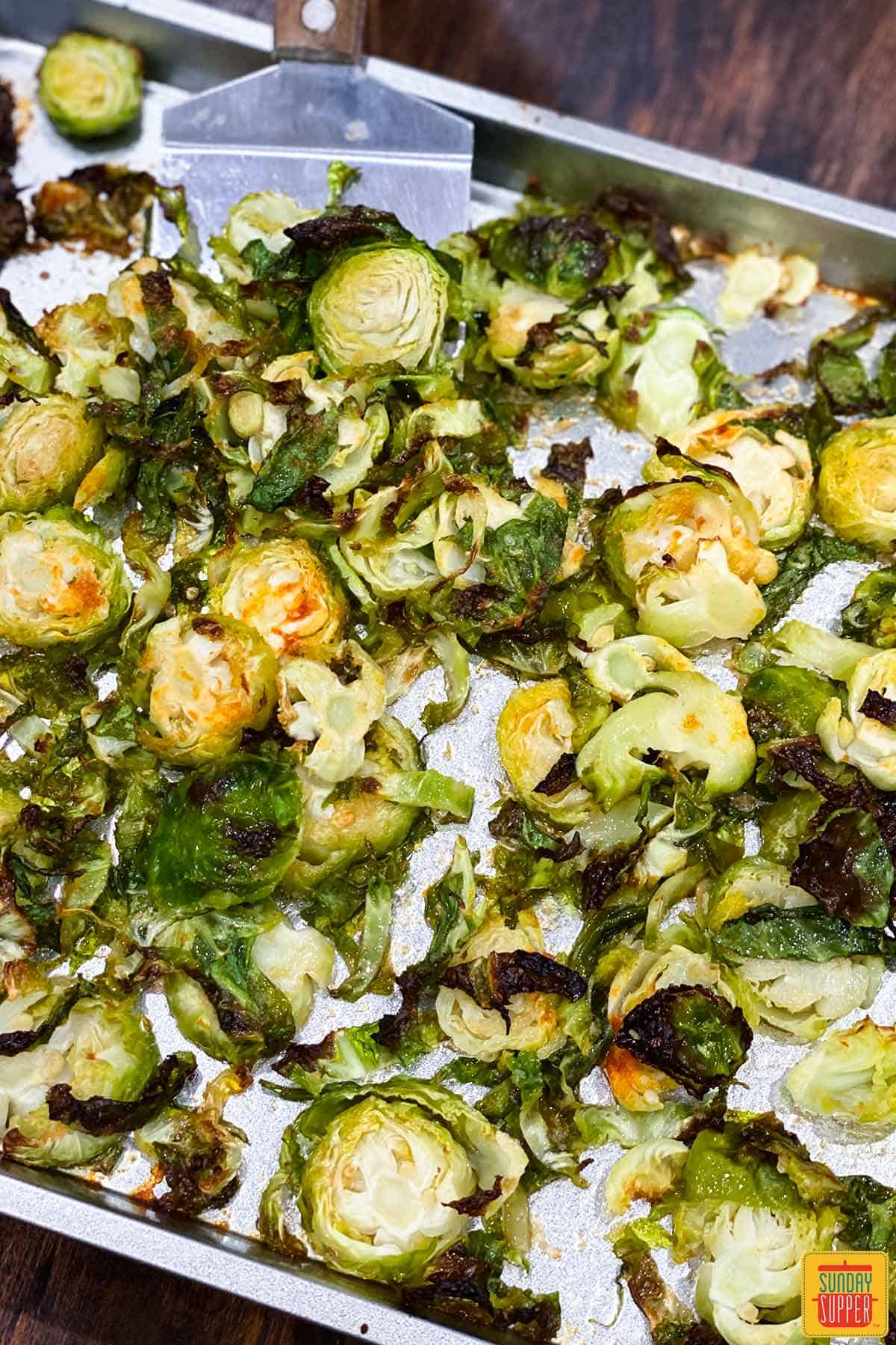 Honey roasted brussels sprouts on a baking sheet with a spatula