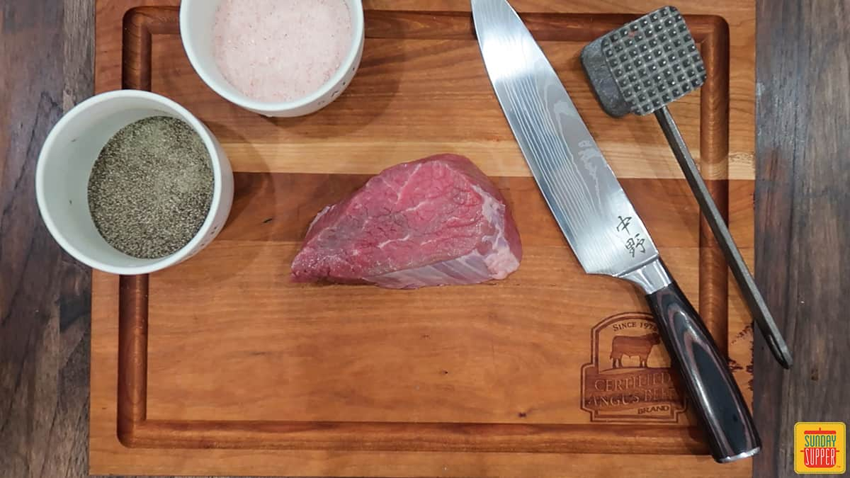 Knife, salt, pepper, meat mallet, and raw steak on a cutting board