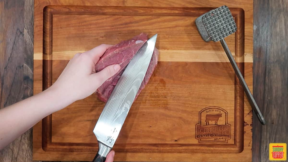 beginning to open the steak with the knife after cutting through it
