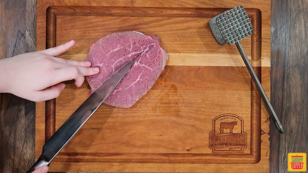 Slicing down the middle of the cut steak to flatten it out