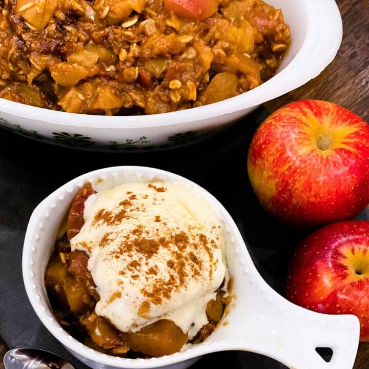 Apple crisp in two white dishes: one has ice cream on top and there are two fresh apples to the side