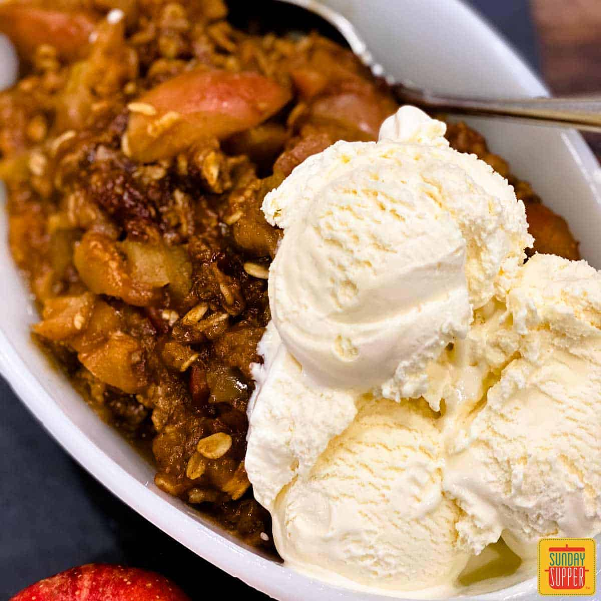 Close up of instant pot apple crisp with ice cream and a spoon