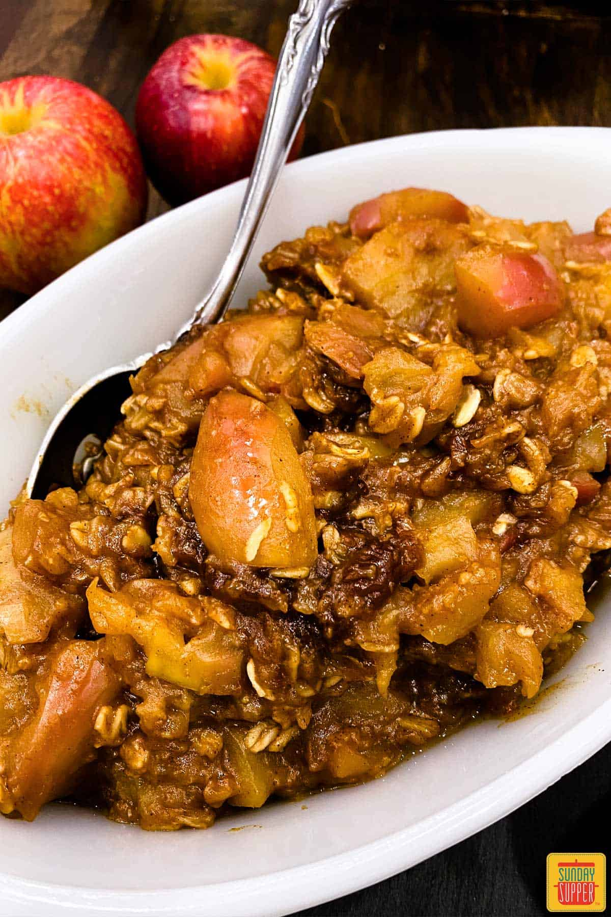 instant pot apple crisp in a white dish with a serving spoon