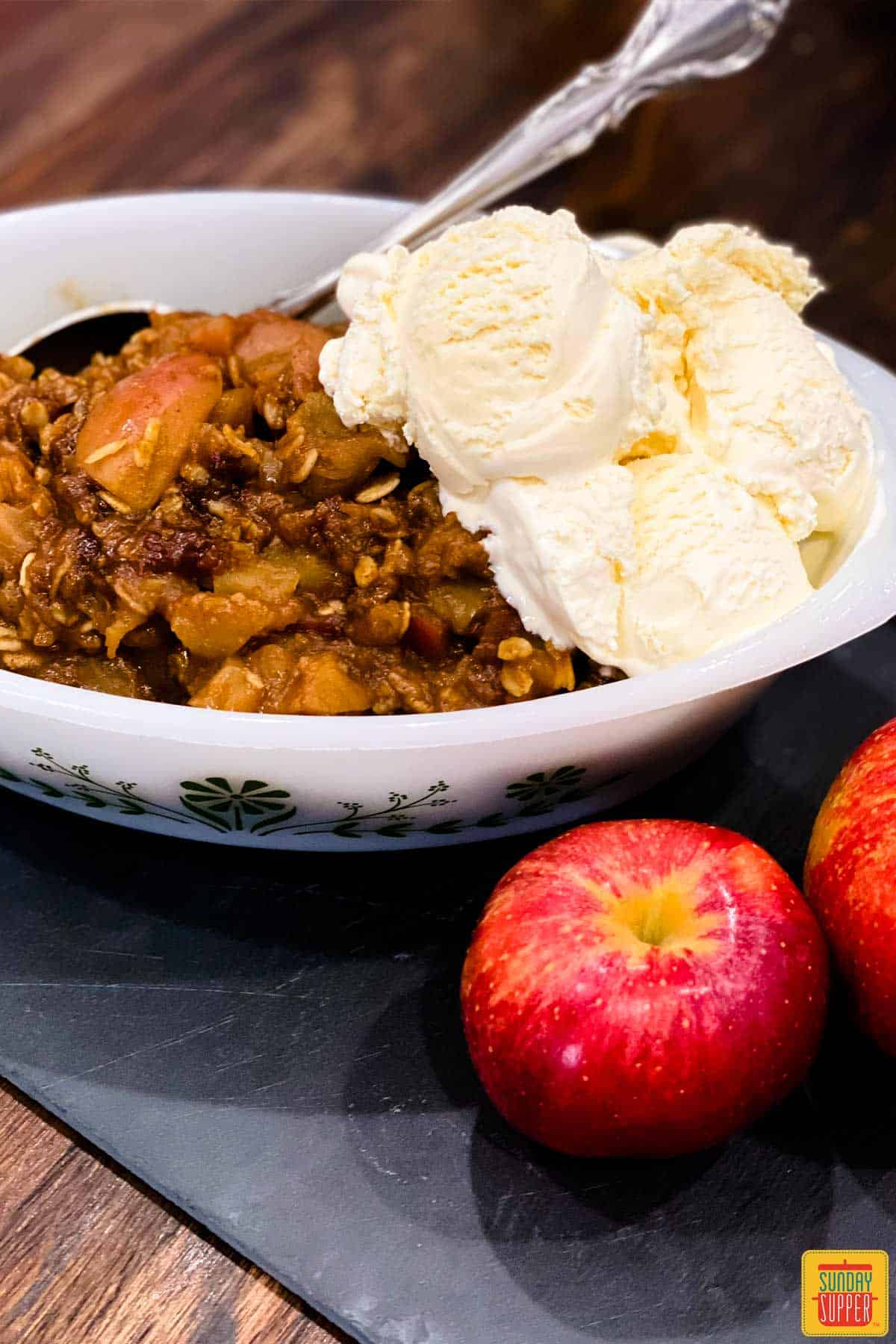 instant pot apple crisp in a white dish with ice cream and two apples to the side