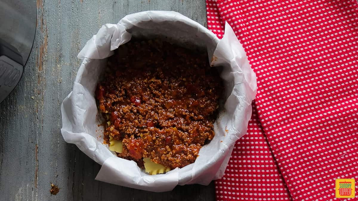a layer of meat sauce over the lasagna noodles