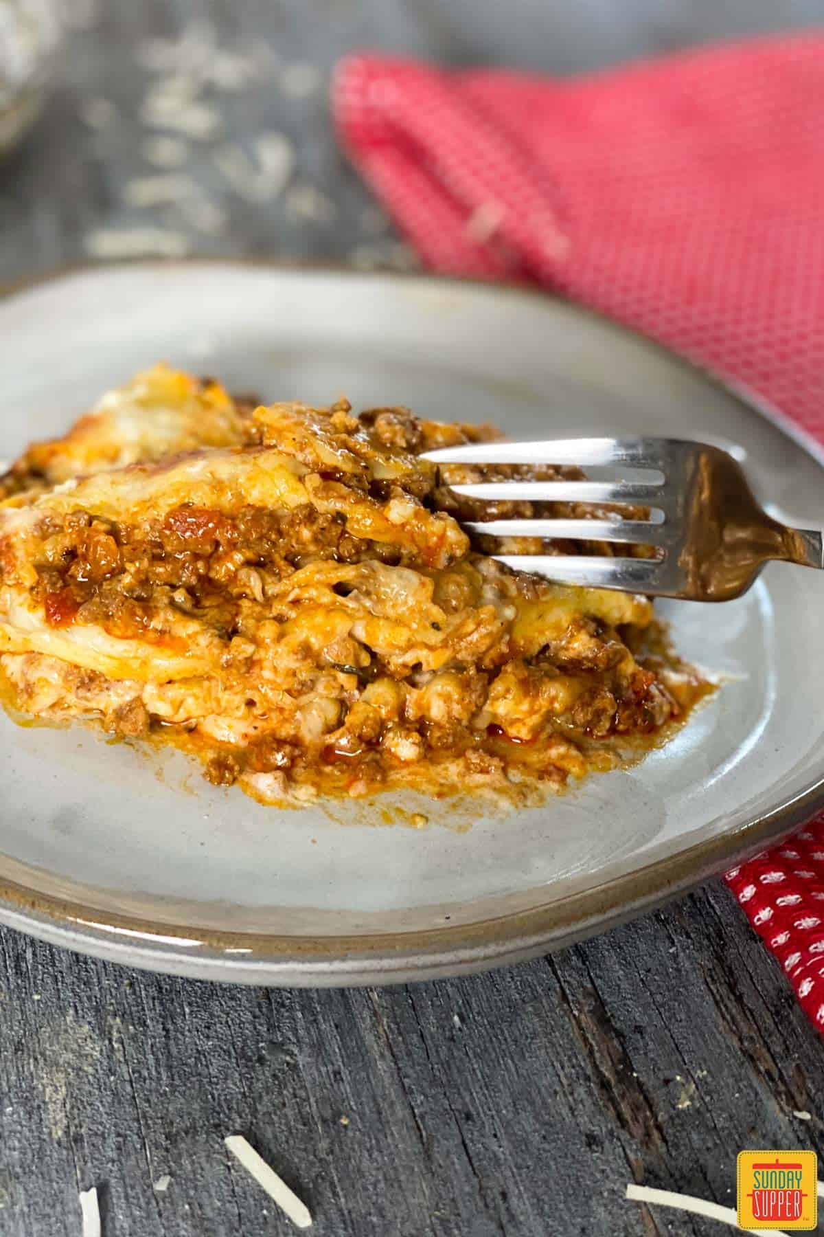 A fork taking a piece of instant pot lasagna on a plate