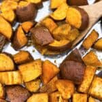 Roasted sweet potatoes with a wooden spoon on a baking sheet