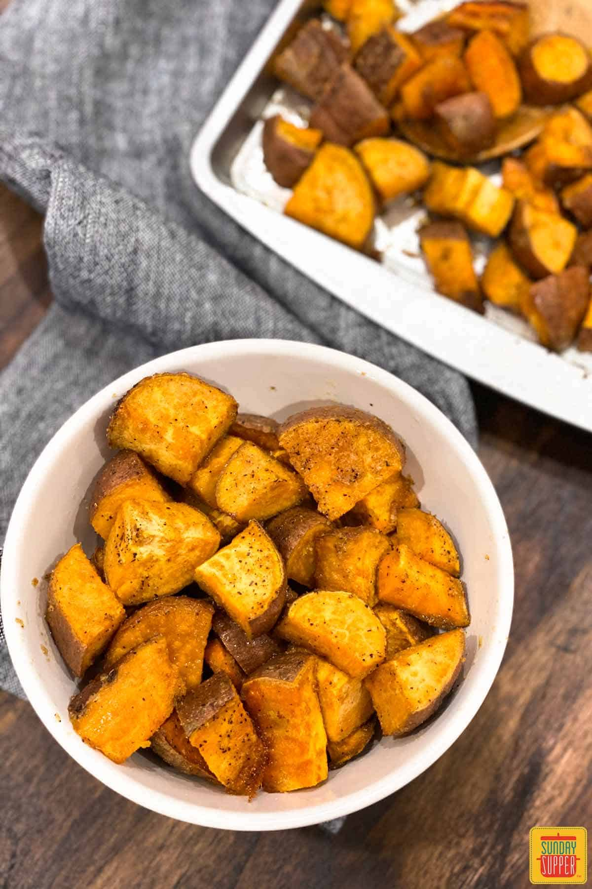 Roasted sweet potatoes in a white bowl and on a baking sheet