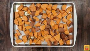 Sweet potatoes tossed with olive oil and maple syrup on a baking sheet