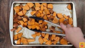 Tossing sweet potatoes with seasoning using tongs
