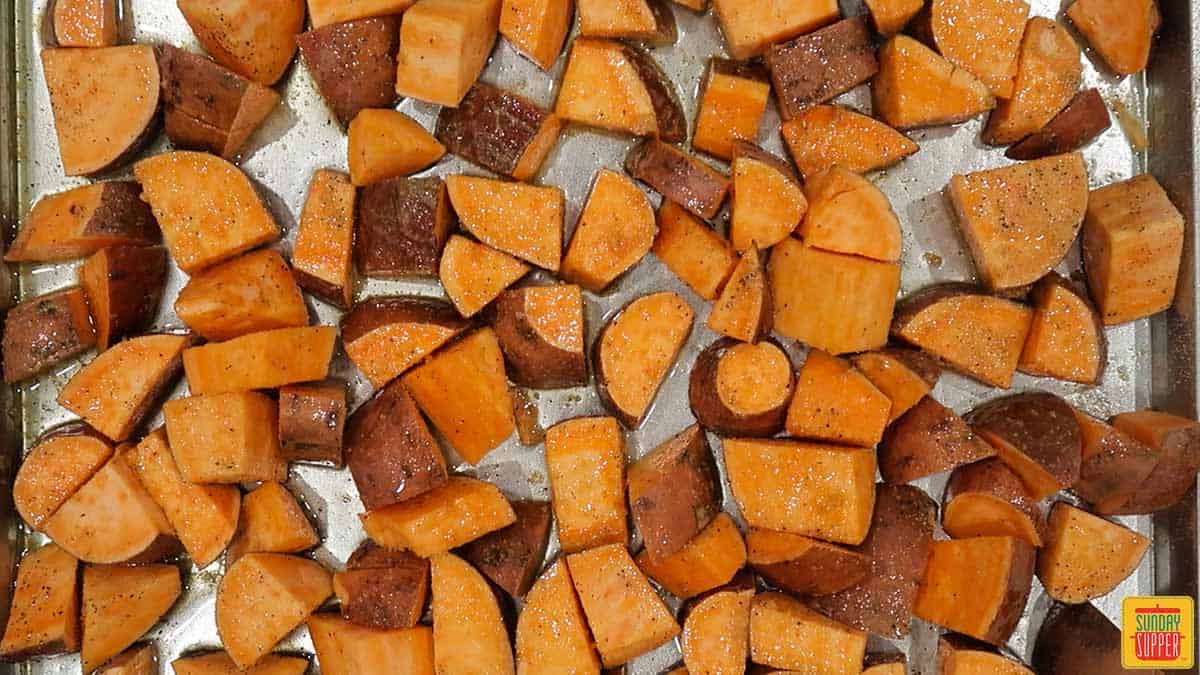 Close up of sweet potatoes on baking sheet ready to be baked