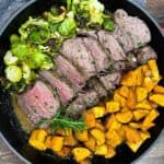 Sous vide beef tenderloine in a skillet with roasted sweet potatoes and brussels sprouts