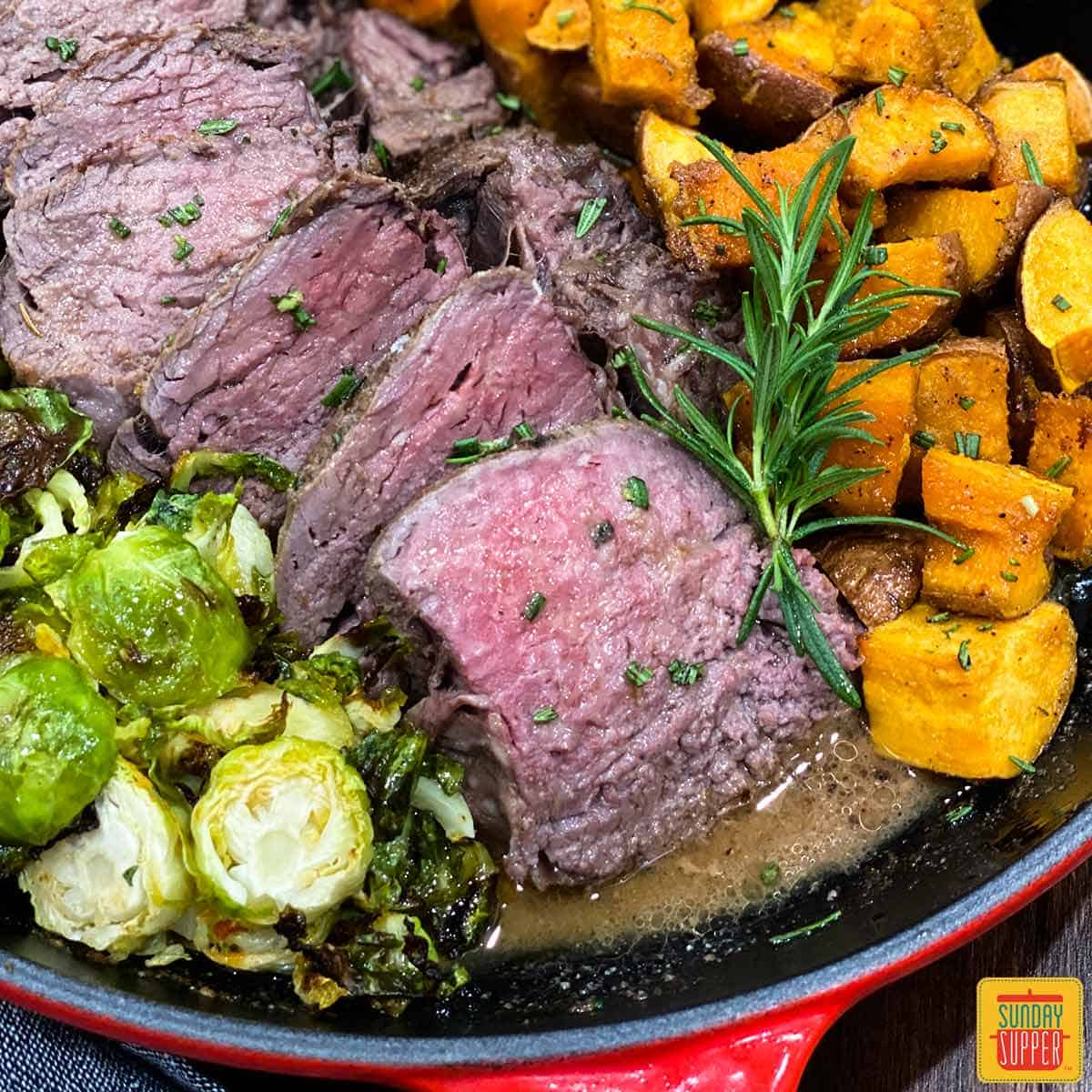 Sliced sous vide beef tenderloin close up in a skillet with roasted sweet potatoes and brussels sprouts