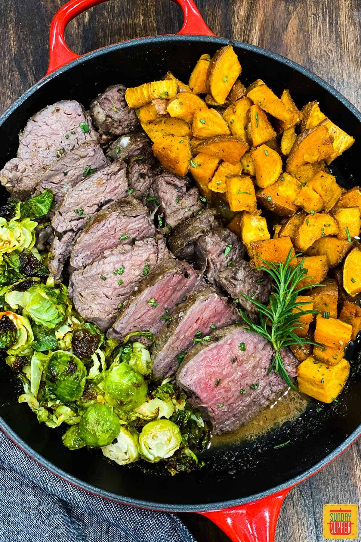Overhead shot of sous vide beef tenderloin in a skillet with sweet potatoes and brussels sprouts