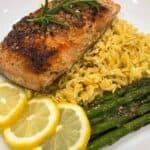 Sous vide salmon next to three lemon slices, orzo, and asparagus
