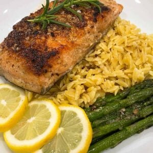 Sous vide salmon next to three lemon slices, orzo, and asparagus