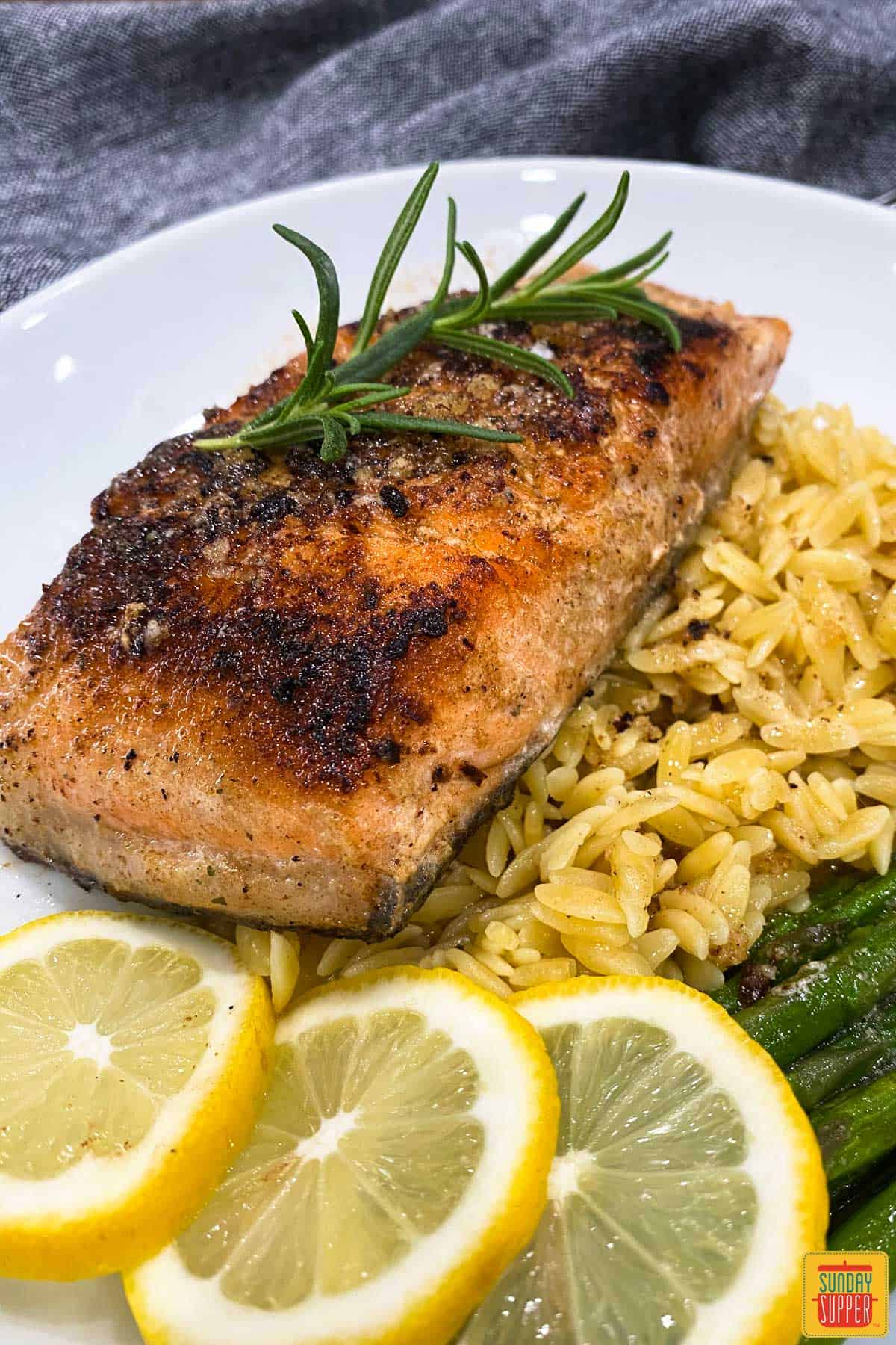 A white plate with sous vide salmon, lemon slices, orzo, and asparagus