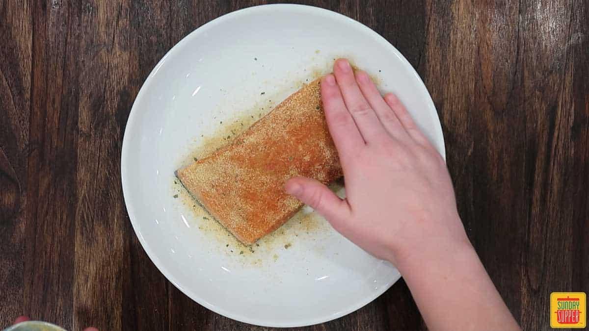 Seasoning salmon fillet on a white plate